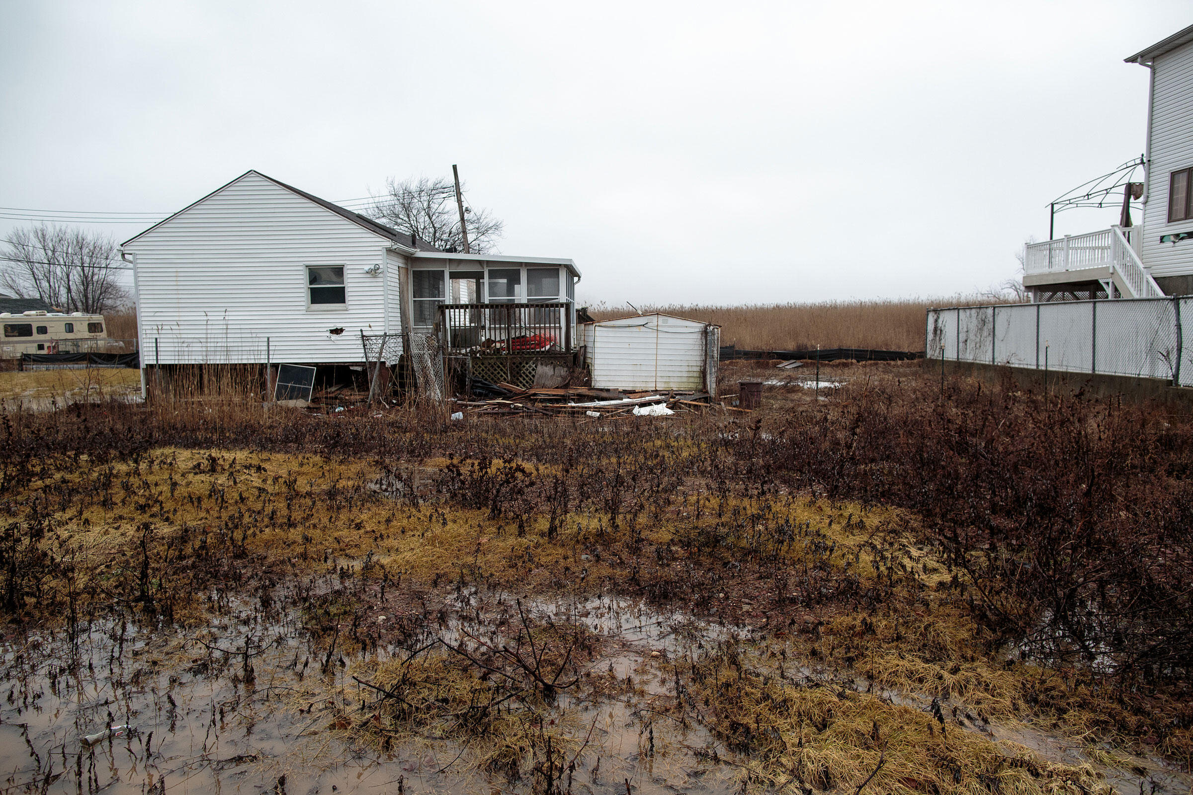 A puddle from the previous night's rain gathers in the yard of a water-damaged house, returning the land to the marshland it once was. February 24, 2016. Hillary Eggers