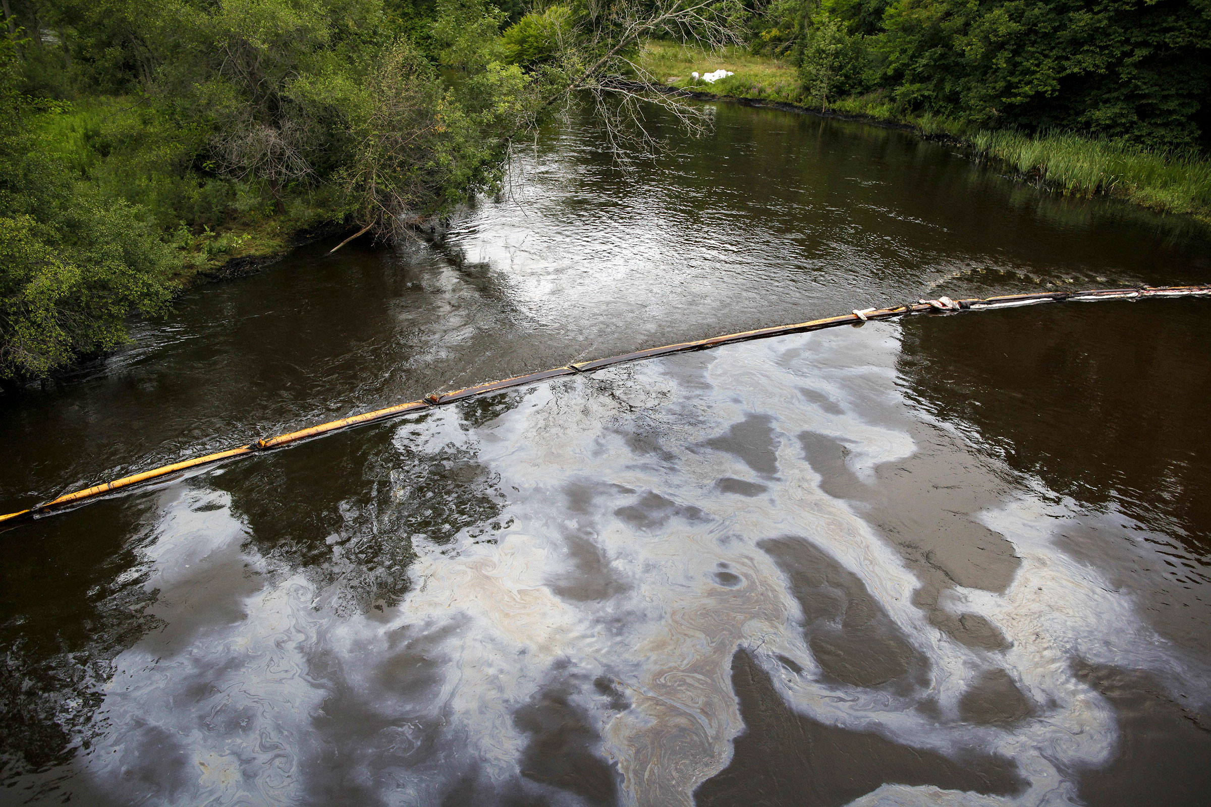 A boom traps oil as it flows down the Kalamazoo River in Michigan, July, 2010, where over 1.2 million gallons of tar sands crude oil were spilled from an Enbridge pipeline. Brian Kersey/UPI/Alamy