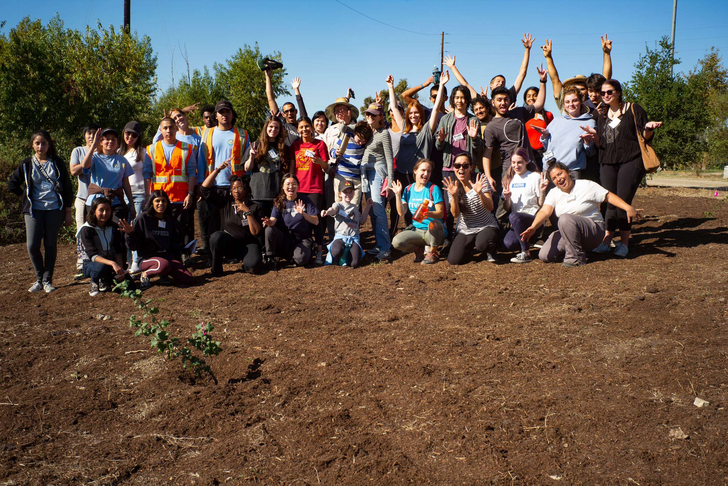 Tania Romero, program coordinator at Audubon Center at Debs Park, bottom right, takes a celebratory picture with students after a successful community habitat enhancement work day at Rio de Los Angeles State Park. Courtesy of Tania Romero