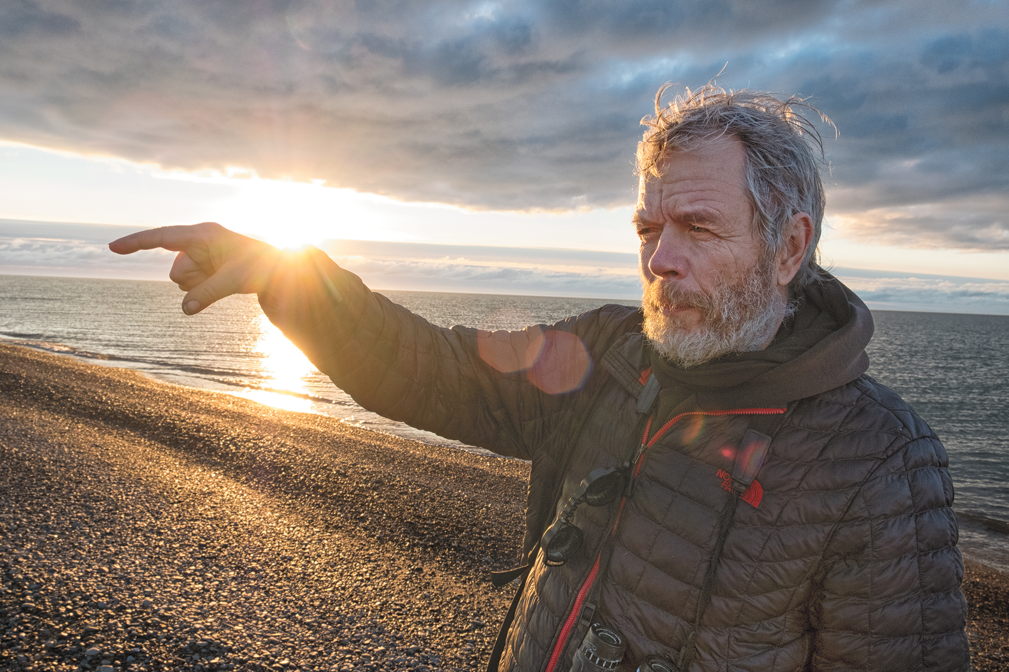 George Divoky gestures by the light of Alaska's midnight sun on Cooper Island. Peter Mather