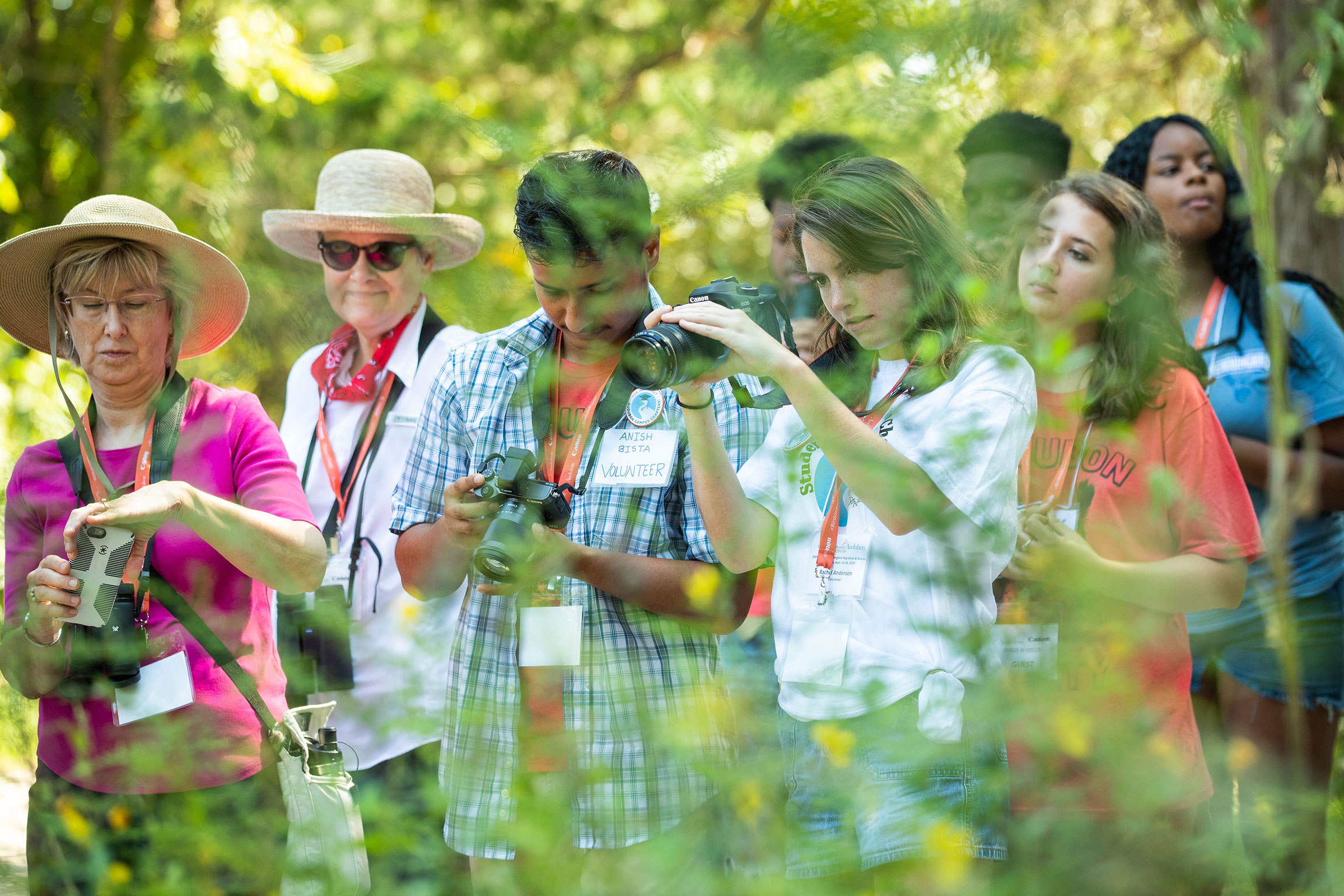 """Anish Bista (Left) and Rachel Anderson (Right), members of the Magnolia Grove Audubon chapter at the University of Mississippi, test out Canon gear on a """"Birds in Focus"""" walk at the Strawberry Plains Hummingbird Festival. Dominic Arenas/Audubon"""