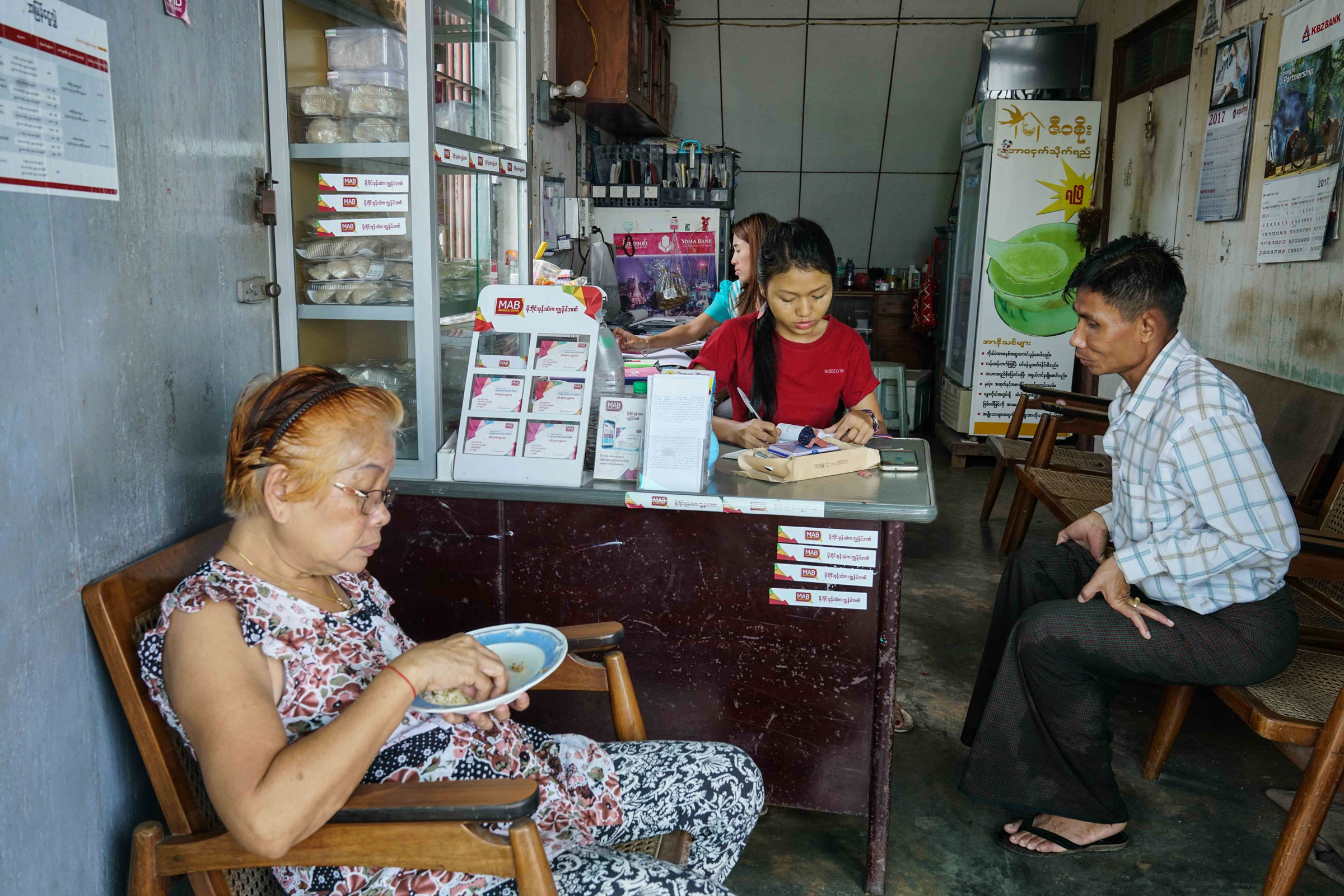 A typical Myanmar house farm (like the one in the video above) has a nesting space on the top floor and a shop on the bottom. Here, owner Daw Myint Win (in the foreground) presides over a busy afternoon of business. Aung Naing Soe