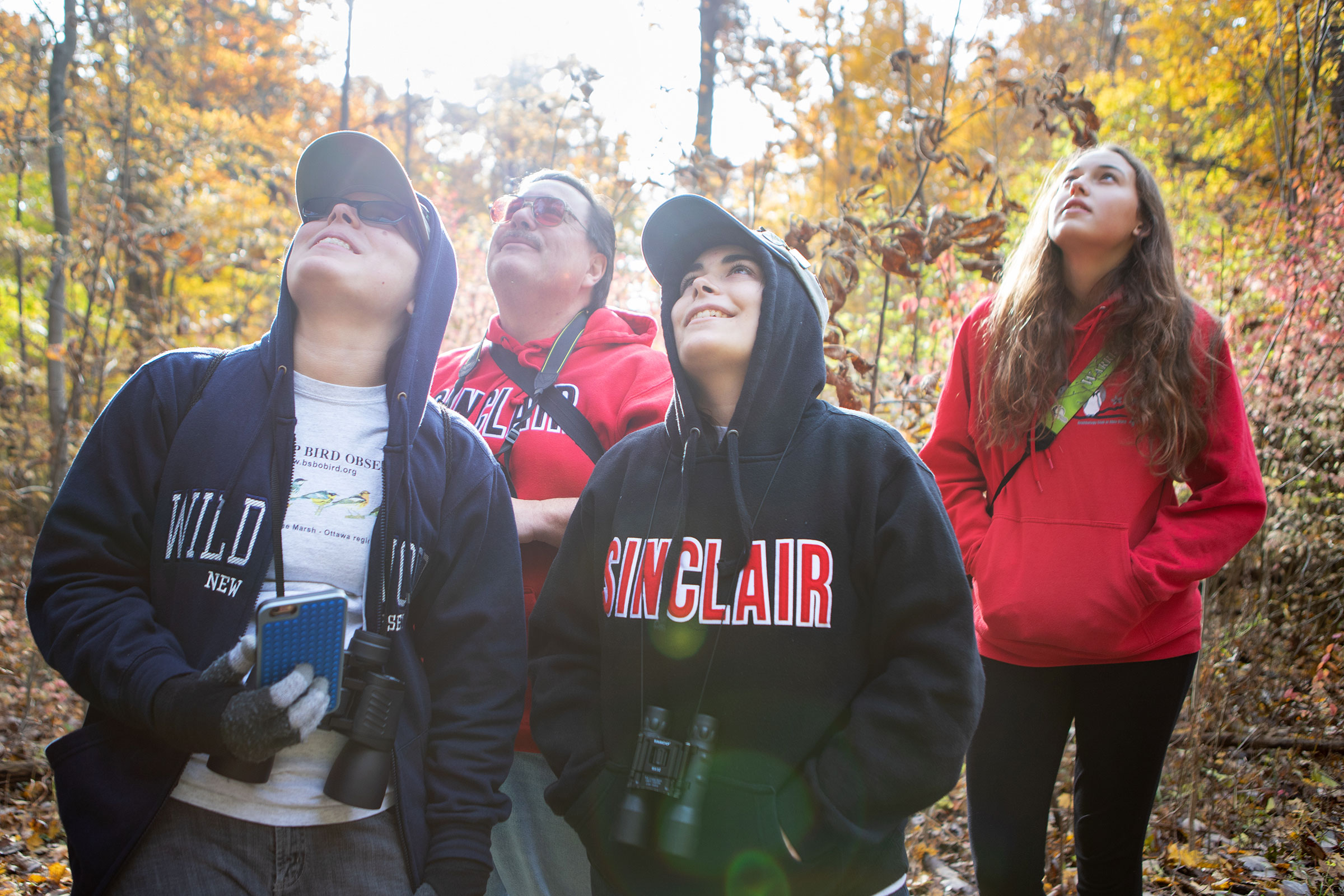 Young birders (from left) Christina Price and Danielle Price, along with their dad, join Cassidy Ficker on a field trip at the Blendon Woods in Columbus, Ohio. Camilla Cerea/Audubon
