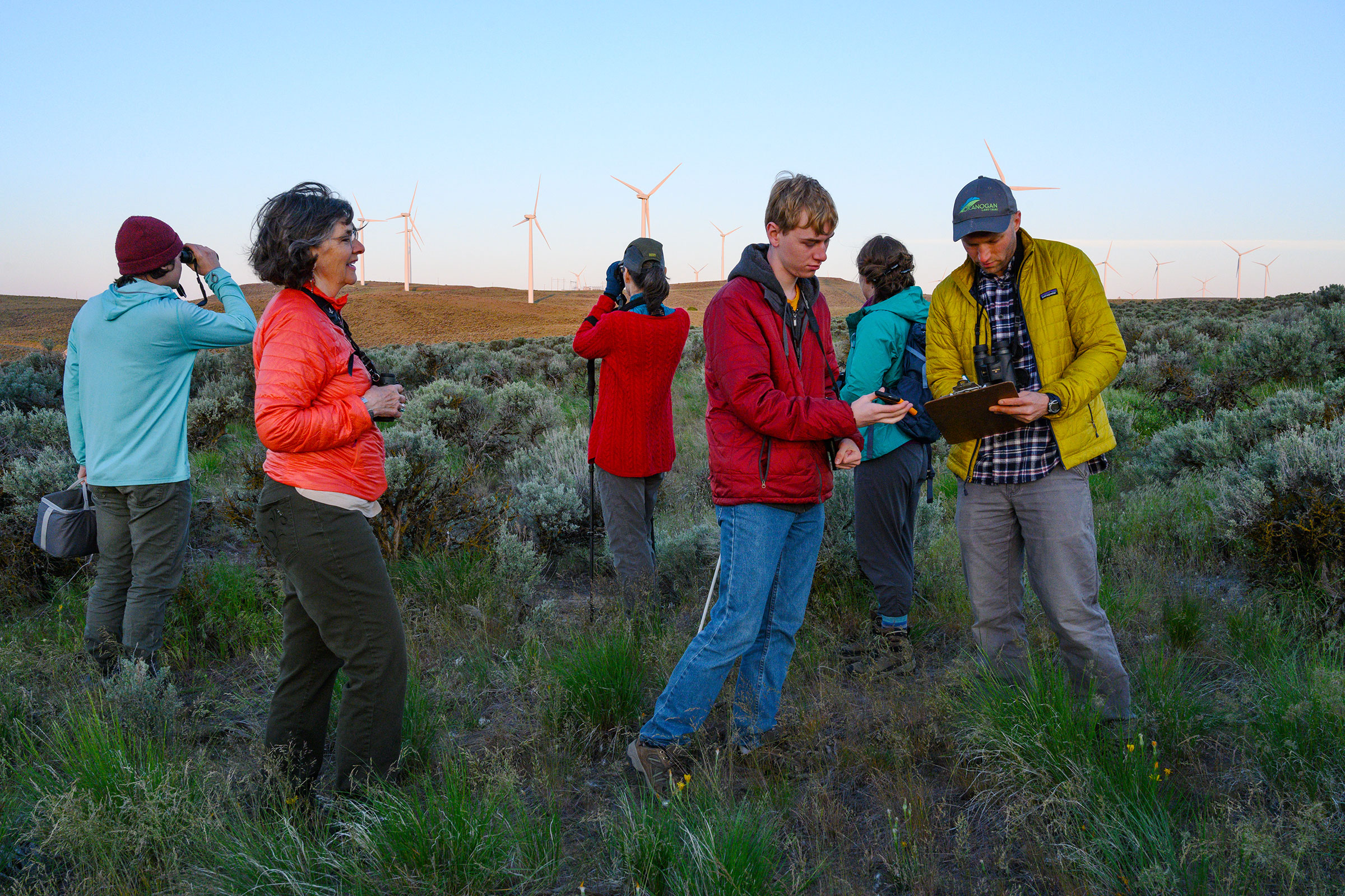 A Sagebrush Songbird Survey group hits the Wild Horse Wind and Solar Facility in Kittitas County, Washington, at first light. In front, Christi Norman observes as volunteers Curtis Mahon and John Rohrback record data. Dave Showalter